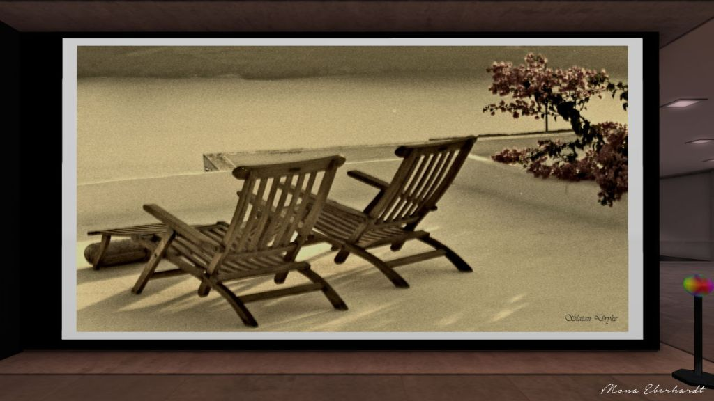 Black and white photograph of two wooden beach chairs on an Aegean patio.